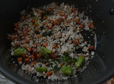mixing salt, suagr and beaten rice for avalakki upkari or poha snacks