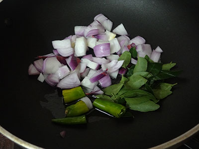 frying onion, chili and curry leaves for mixed flour poori or hittina vade
