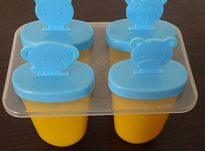 pour mango puree into popsicle moulds for mango popsicles