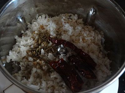 grind coconut and red chili for padavalakai palya or snake gourd stir fry