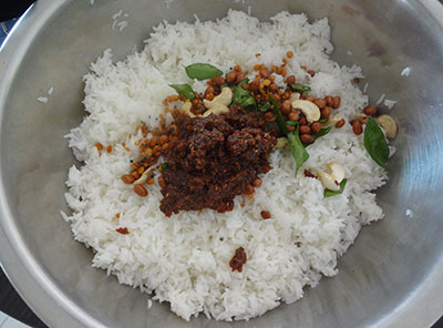 mixing puliyogare or tamarind rice